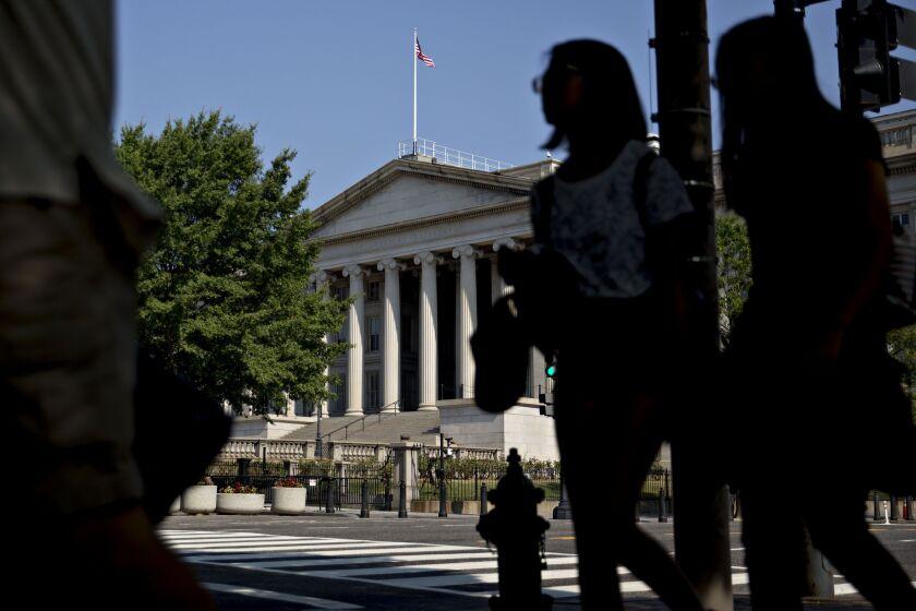 Pedestrians walk near the U.S. Treasury building in Washington, D.C.