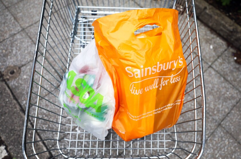 An Asda plastic carrier bag, left, and a Sainsbury's plastic carrier bag, right, sit in a supermarket trolley in this arranged photograph in Watford, U.K.