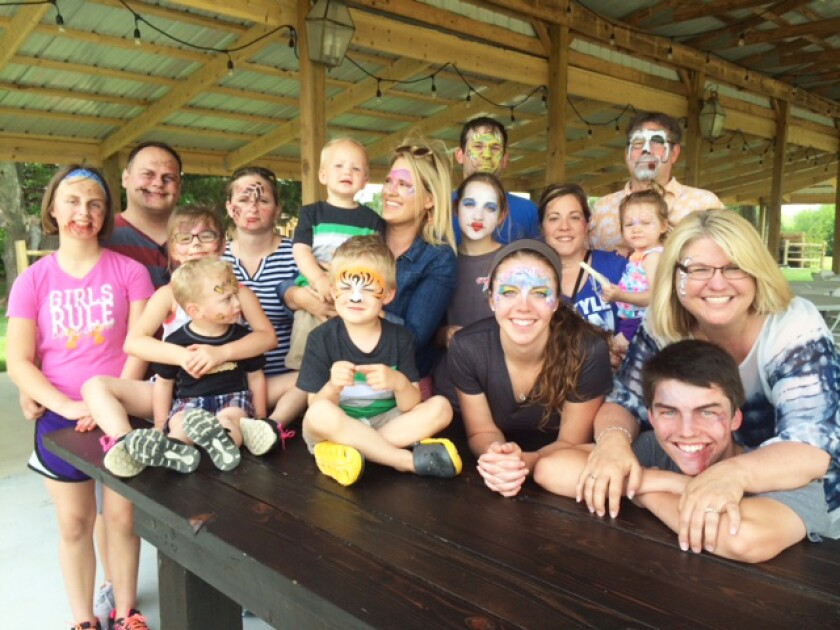 Staff and family at Allen, Gibbs & Houlik enjoy face painting at a family picnic
