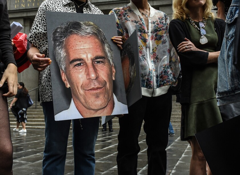A protest group hold up signs of Jeffrey Epstein in front of the Federal courthouse in New York.