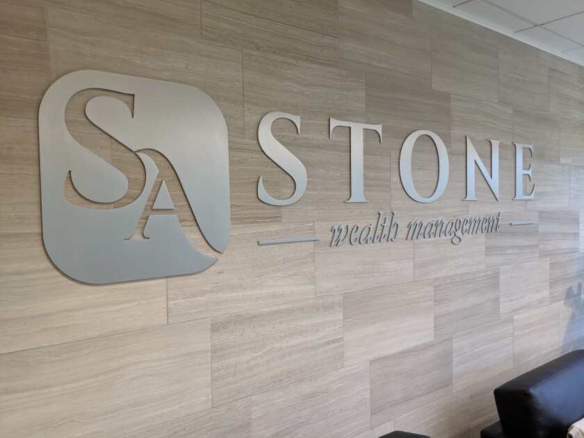 A photo of the SA Stone Wealth Management logo in its lobby