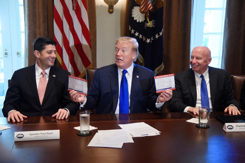 """U.S. President Donald Trump, center, speaks while holding up """"Simple, Fair, 'Postcard' Tax Filing"""" cards as U.S. House Speaker Paul Ryan, a Republican from Wisconsin, left, and Representative Kevin Brady, a Republican from Texas and chairman of the House Ways and Means Committee, react during a meeting in the Cabinet Room of the White House in Washington, D.C., U.S., on Thursday, Nov. 2, 2017. The House tax bill released Thursday preserves the carried interest tax break despite Trump and GOP leaders' promise to do away with loopholes for the wealthy."""