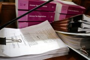 "A printout of Congress's tax reform bill, ""The Tax Cuts and Jobs Act,"" alongside a stack of income tax regulations"