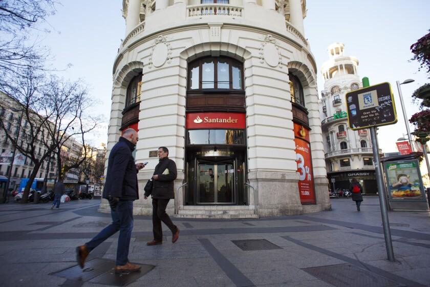 Pedestrians pass a Banco Santander SA bank branch in Madrid, Spain.