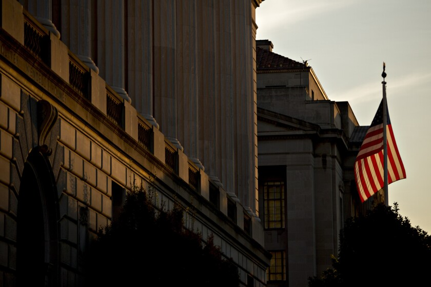 An American flag flies outside the Internal Revenue Service headquarters at sunrise in Washington, D.C.