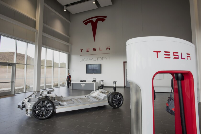 A vehicle charger, right, stands in the lobby at the Tesla Motors Inc. Gigafactory in McCarran, Nevada.