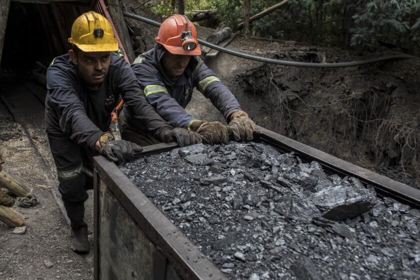 Miners push a wagon of coal outside a mine in Cucunuba, Cundinamarca Department, Colombia, on Friday, July 28, 2017. Colombia is set to produce a record of more than 90 million tons of the fossil fuel this year, its biggest export after oil. Colombia continues to bet on coal, even as global demand tapers off because the world is switching to cleaner fuels. Photographer: Nicolo Filippo Rosso/Bloomberg