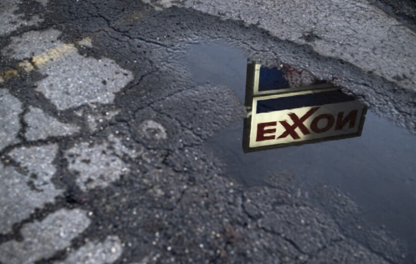 Exxon Mobil sign reflected in a puddle at a gas station in Nashport, Ohio