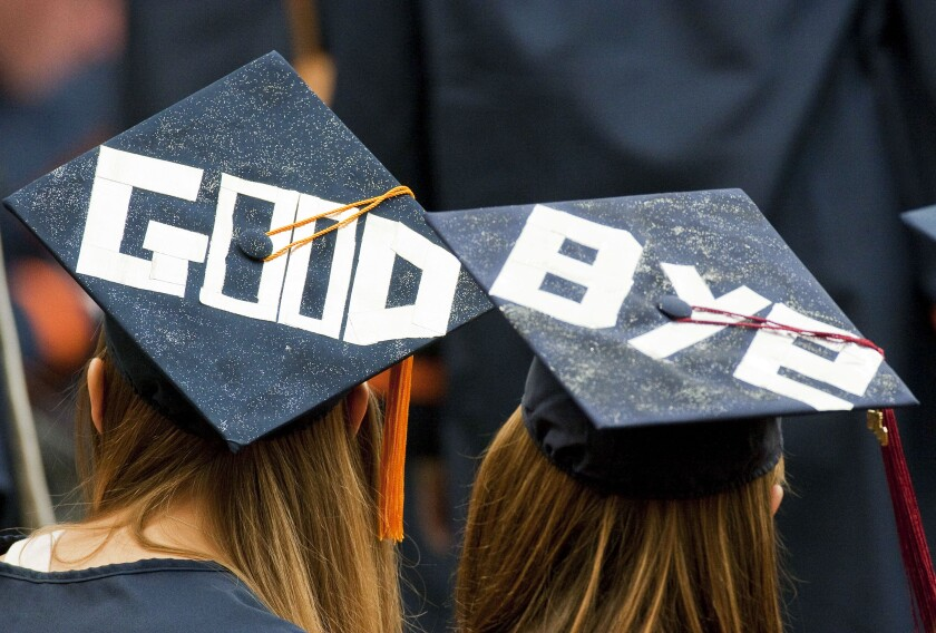 "Students at graduation with ""good-bye"" on their hats"