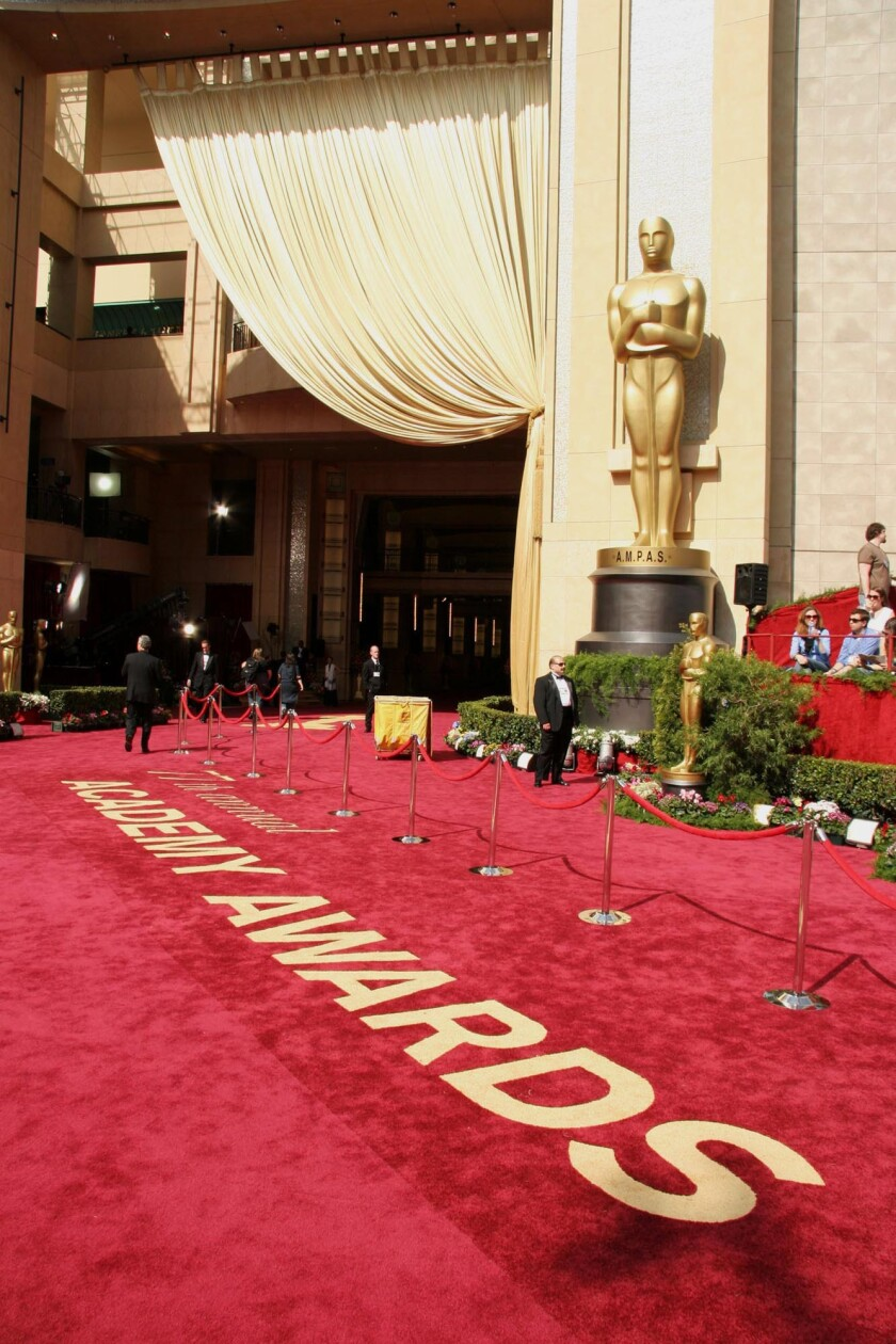 An Oscar statue stands next to the red carpet entrance to Academy Awards.