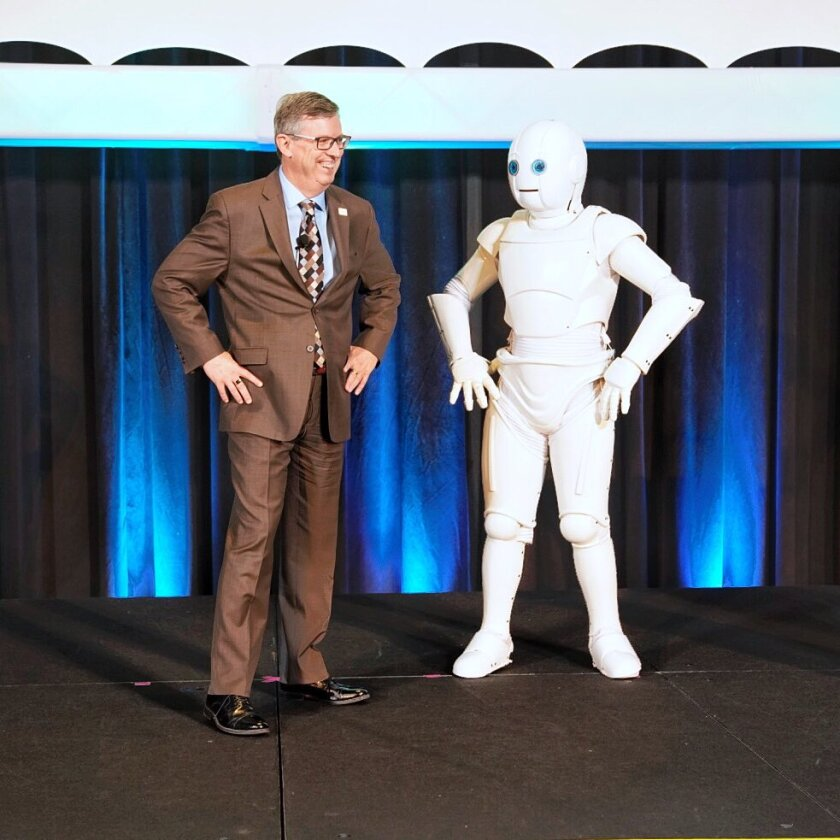 Institute of Management Accountants president and CEO Jeff Thomson with a robot at the IMA's annual conference in Indianapolis