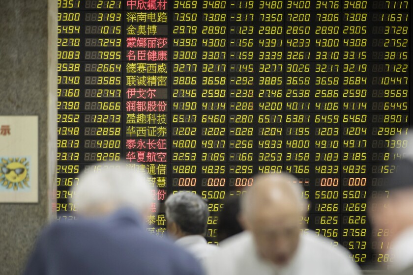 Investors stand in front of an electronic stock board at a securities brokerage in Shanghai.