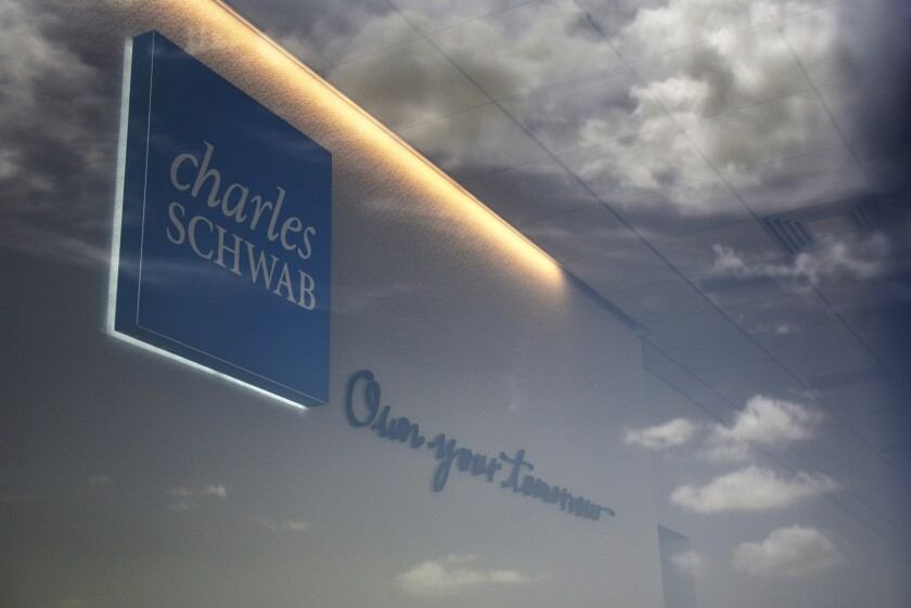 Clouds are reflected in the window of a Charles Schwab Corp. location in San Antonio, Texas, U.S., on Sunday, July 15, 2018. Charles Schwab Corp. is scheduled to release earnings figures on July 17. Photographer: Callaghan O'Hare/Bloomberg News