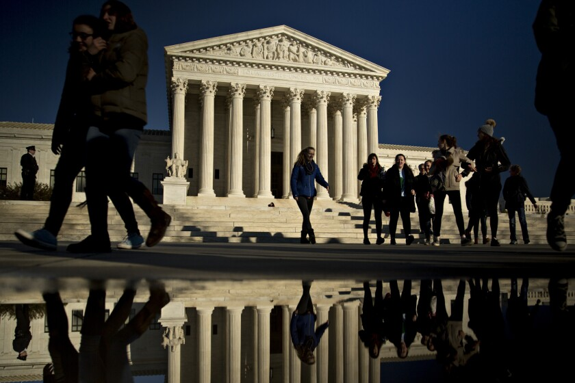 Visitors walk in front of the U.S. Supreme Court building in Washington, D.C.