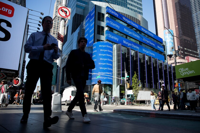 Pedestrians pass monitors displaying signage outside of Morgan Stanley global headquarters in New York, U.S., on Monday, Oct. 14, 2019. Morgan Stanley is scheduled to release earnings figures on October 17. Photographer: Michael Nagle/Bloomberg