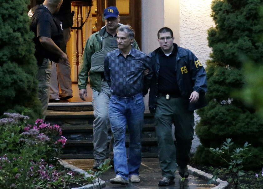 Vitaly Korchevsky is escorted in handcuffs from his home by agents from the Federal Bureau of Investigation (FBI) in Glen Mills, Pennsylvania, U.S., on Tuesday, Aug. 11, 2015. Korchevsky, 50, was one of several men arrested Tuesday morning in the biggest case of insider trading linked to the fast-growing threat of global cybercrime. The alleged scheme stretched from the affluent suburbs of Philadelphia, where Korchevsky ran the small investment firm NTS Capital Fund, to the darkest realms of the Internet.