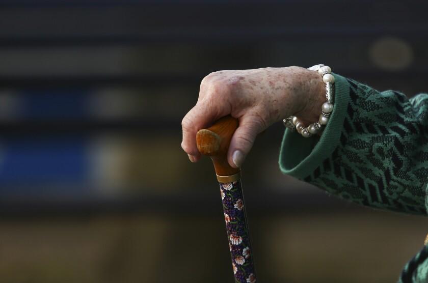 Eldlery woman holding cane Bloomberg News image