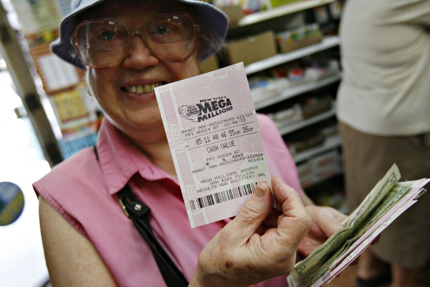 Heidi Urban holds up her Mega Millions ticket after purchasing it at L&P Stationery in Queens, New York, Aug. 24, 2007 Bloomberg News