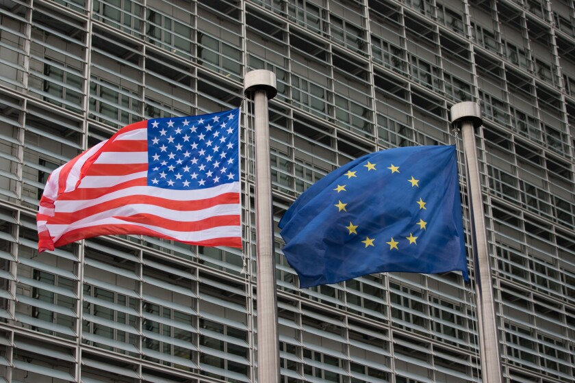 The U.S. flag flies beside a European Union flag outside the European Commission building in Brussels.