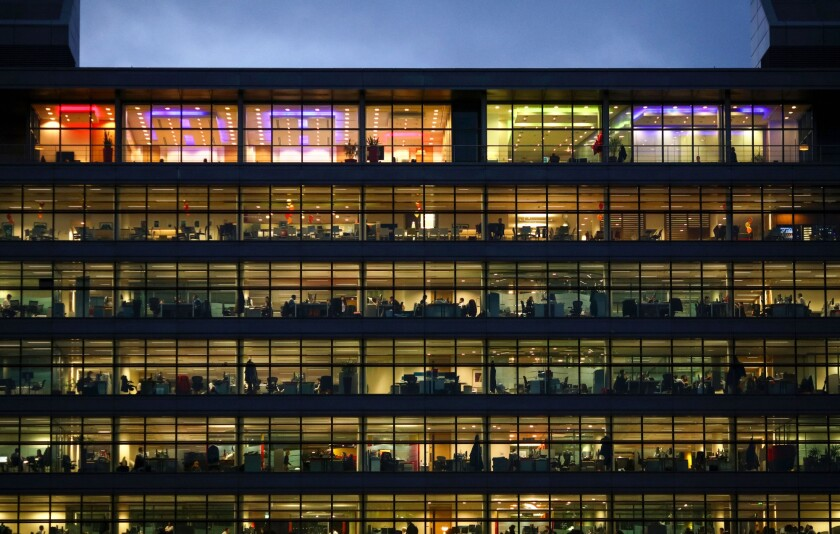 Electric lights illuminate office workers inside PwC's building in Dublin