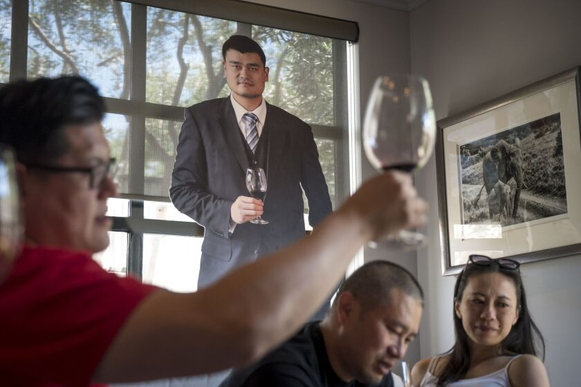 Patrons taste wine inside the Yao Family Wines tasting room in St. Helena, California.