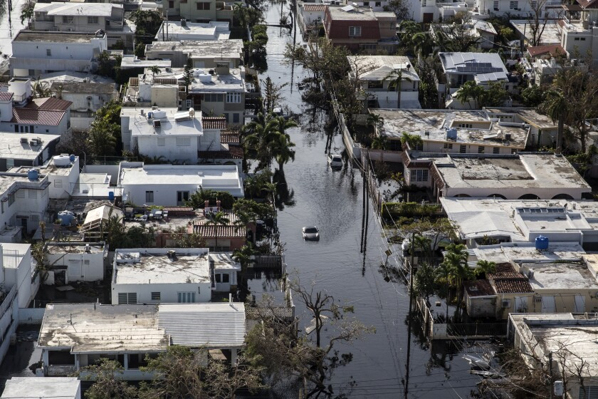 A vehicle drives through streets filled with floodwater and past destroyed homes caused by Hurricane Maria in this aerial photograph taken above Barrio Obrero in San Juan, Puerto Rico, on Monday, Sept. 25, 2017.