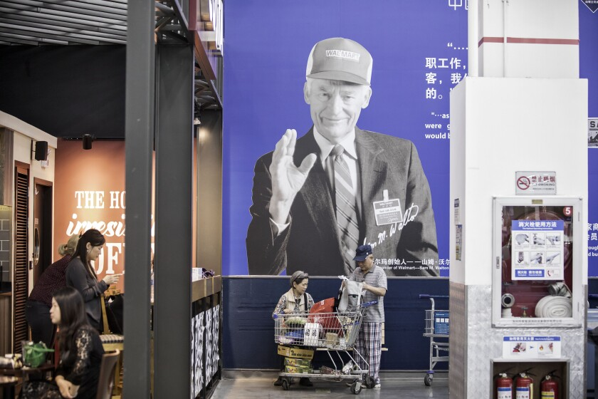 Customers arrange a shopping cart in front of an advertisement featuring the photograph of Wal-Mart Stores Inc. founder Sam Walton at the company's Sam's Club store in Shenzhen, China, on Tuesday, Oct. 18, 2016. Wal-Mart sees big potential in China: its Sam's Club in Shenzhen, a fast-growing urban center in the southeast, is the chain's best-performing outlet globally. Photographer: Qilai Shen/Bloomberg