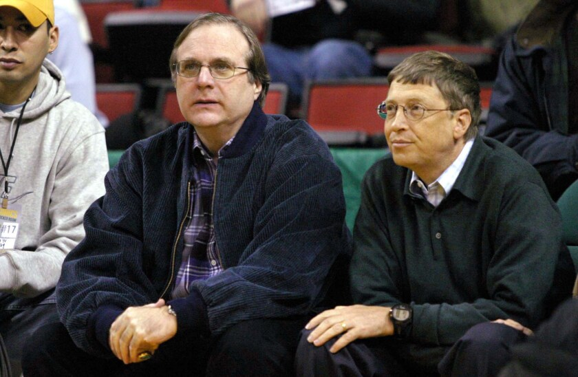 Paul Allen, owner of the Portland Trail Blazers and co-founder of Microsoft Corp., left, sits with Bill Gates, chairman and co-founder of Microsoft Corp., during a Blazers basketball game at the Key Arena in Seattle in 2004.