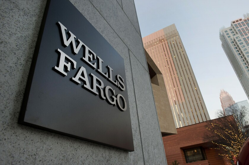 Wells Fargo & Co. signage is displayed outside of the Duke Energy Center building in Charlotte, North Carolina, U.S., on Thursday, Dec. 13, 2012. The new Wells Fargo & Co. expanded trading floor, which opened on Dec. 10, is located in the Duke Energy Center. Photographer: Davis Turner/Bloomberg