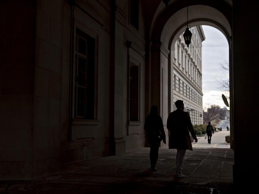Pedestrians walk through the IRS headquarters in Washington, D.C.