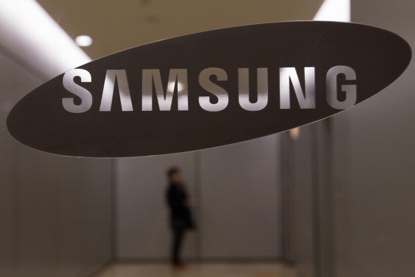 A woman waits for an elevator behind a Samsung Electronics Co. logo displayed at the company's Seocho office building in Seoul.