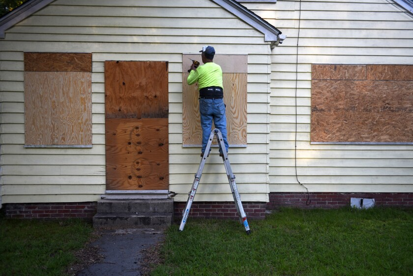 """A man secures plywood to protect a window of a property ahead of Hurricane Florence in Greenville, North Carolina, U.S., on Wednesday, Sept. 12, 2018. Hurricane Florence is slowing as it advances upon the U.S. Southeast, promising """"disaster"""" for residents near the Carolina coast. Photographer: Callaghan O'Hare/Bloomberg"""