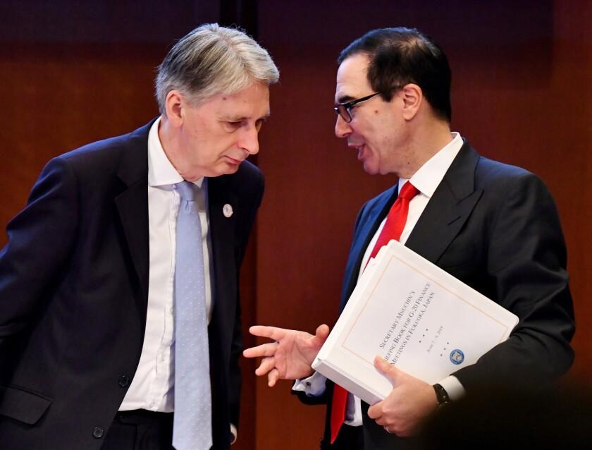 Steven Mnuchin, U.S. Treasury secretary, right, speaks with Philip Hammond, U.K. chancellor of the exchequer, at the 2019 G20 summit