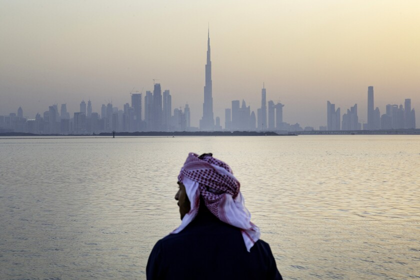 An Emirati man looks out from the Dubai Creek Harbour Development towards the Burj Khalifa tower, center, and other skyscrapers in Dubai, United Arab Emirates.