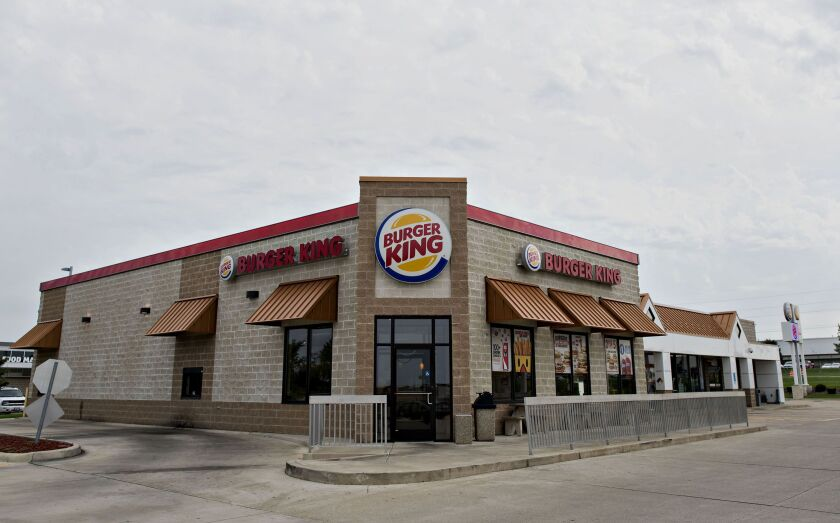 A Burger King Worldwide Inc. restaurant stands in Peoria, Illinois, U.S., on Tuesday, Aug. 26, 2014. Warren Buffett's Berkshire Hathaway Inc. is providing financing for Burger King Worldwide Inc.'s planned takeover of Tim Hortons Inc., the latest deal being backed by a commitment from the billionaire. Photographer: Daniel Acker/Bloomberg