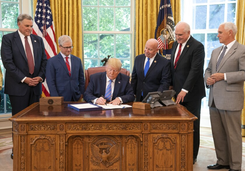 President Trump signing the Taxpayer First Act into law surrounded by IRS Commissioner Charles Rettig, House Ways and Means ranking Republican Kevin Brady, R-Texas, and Mike Kelly, R-Pa., and Vice President Mike Pence.