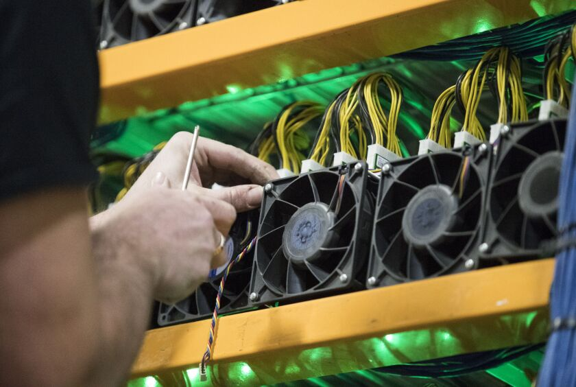 A worker changes the fan on a miner, the computing power to the cryptocurrency farming operation seen at Bitfarms in Farnham, Quebec, Canada, on Wednesday, January 24, 2018.  Photographer: Christinne Muschi/Bloomberg