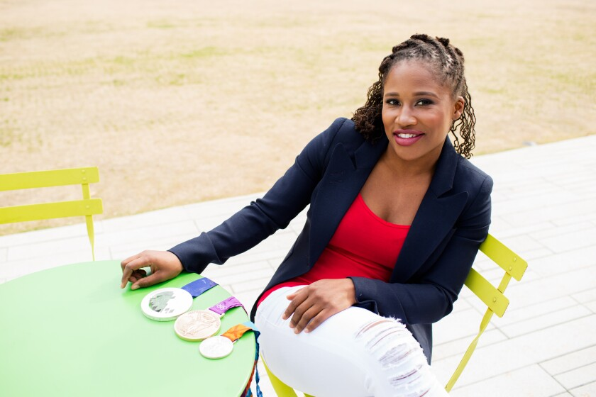 CFP Lauryn Williams sits with the three Olympic medals she has won in track and bobsled.