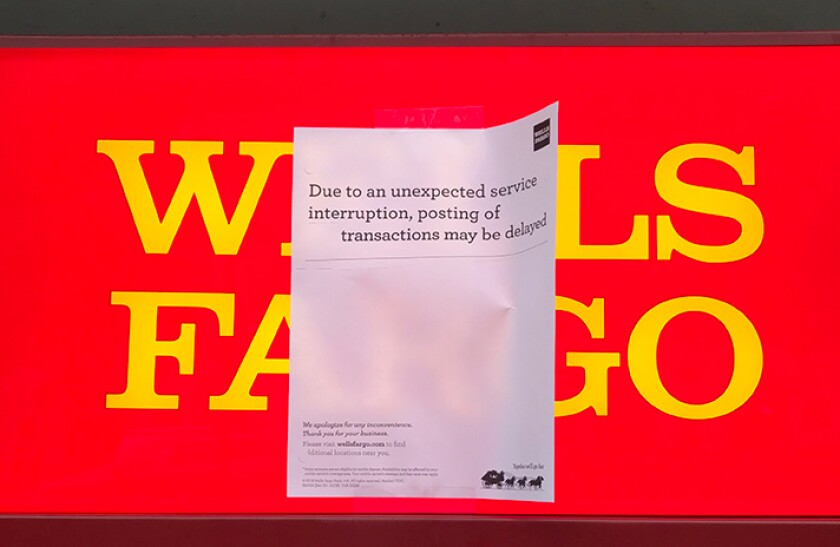 Sign posted on a Wells Fargo ATM alerted customers to potential transaction delays.