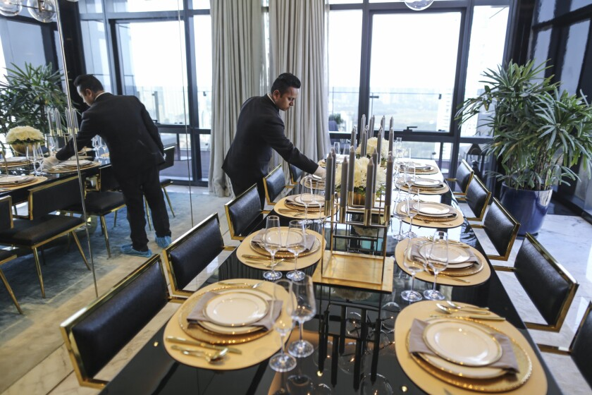 An employee adjusts dinnerware on a table inside a show home at Lodha Altamount a luxury residential project developed by Lodha Developers