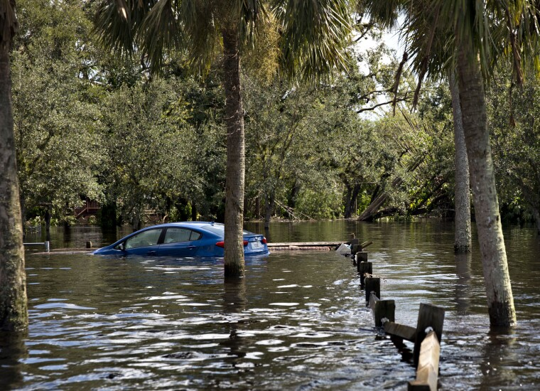 A car sits submerged in flood waters along a road in Buckingham, Florida, U.S., on Tuesday, Sept. 12, 2017