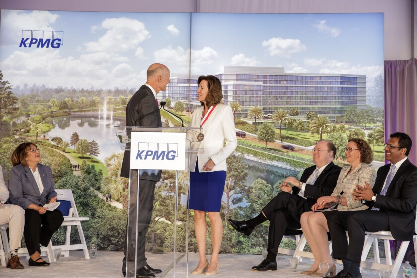 Florida Governor Rick Scott and KPMG CEO Lynn Doughtie, with a depiction of KPMG's upcoming facility in Orlando in the background