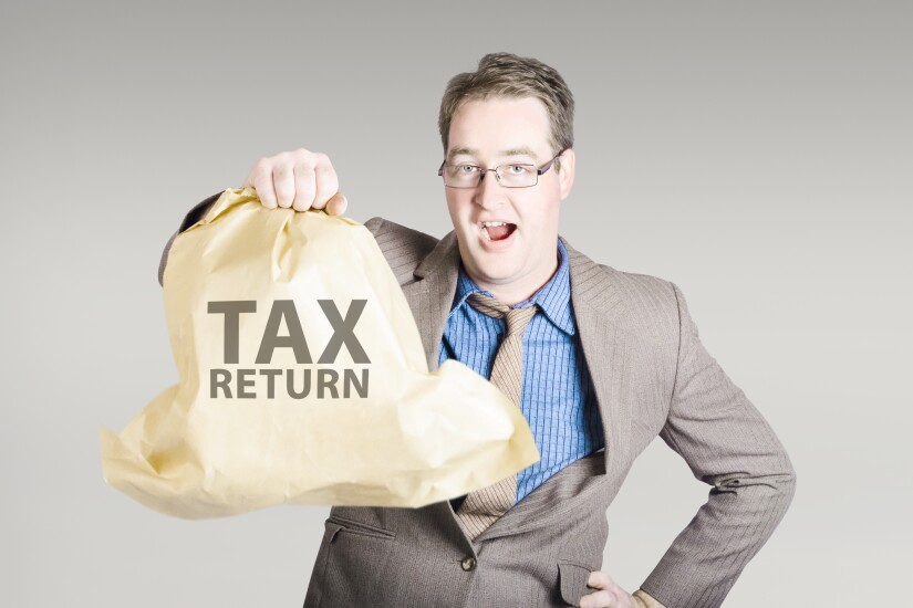 Accountant holding a large tax return refund bag