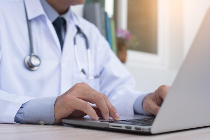 Doctor working on laptop male closeup.jpeg