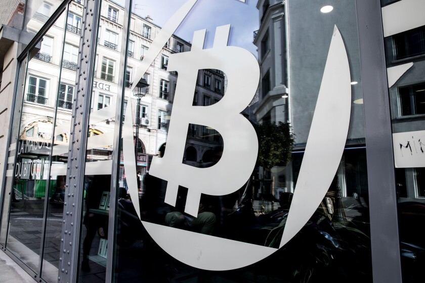 A logo sits on the windows of the offices of La Maison du Bitcoin bank in Paris, France.