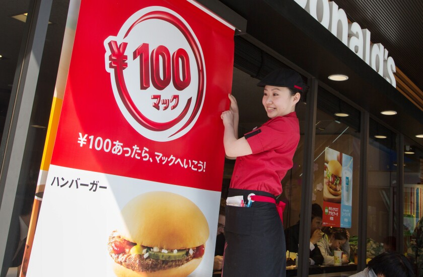 An employee prepares a banner advertising the new price for a hamburger at a McDonald's restaurant, operated by McDonald's Holdings Co. Japan Ltd., in Tokyo, Japan, on Tuesday, April 1, 2014. While McDonald's Japan business will raise prices of most menu items to reflect Japan's sales-tax increase, the restaurant chain will cut the price of a hamburger to 100 yen from 120 yen.