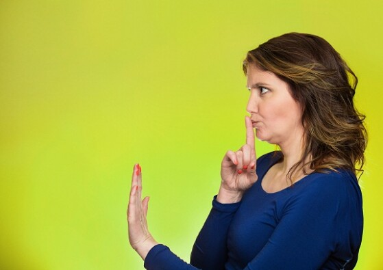 Closeup side view profile portrait serious woman finger, hand on lips, shhh gesture asking be quiet silence isolated green background. Negative facial expression sign emotion feelings, body language