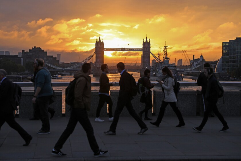 Commuters walk across London Bridge against a backdrop of Tower Bridge.