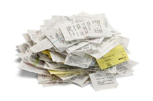 Heap of paper sales receipts in a mound isolated on white background.