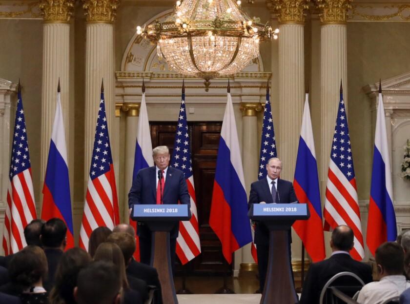 U.S. President Donald Trump, left, listens as Vladimir Putin, Russia's President, speaks during a news conference in Helsinki, Finland.